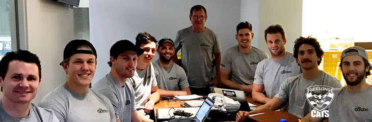 Members of the Geelong Cats team are pictured seated around a table, studying with The Gordon TAFE to attain real skills for their future employment